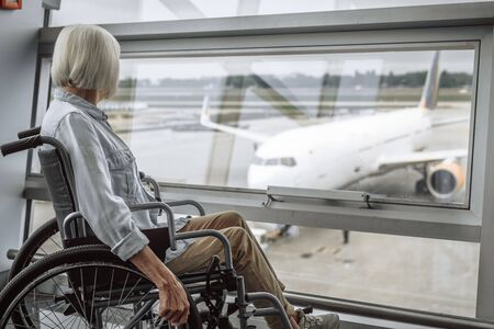 Cheerful mature lady on disabled carriage in airport Stock Photo