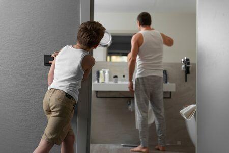 Dad brushing his teeth in bathroom at home
