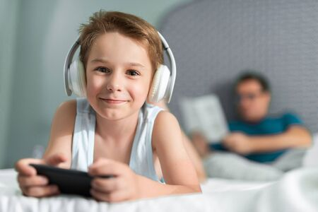 Happy little boy in headphones listening to music in room