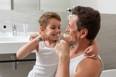 Happy dad and smiling son brushing their teeth