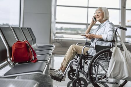 Smiling mature lady on disabled carriage using phone