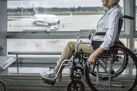 Cheerful mature lady on disabled carriage moving in airport Stock Photo