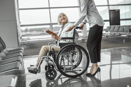 Female worker of airport talking to elderly lady in wheelchair Stock Photo