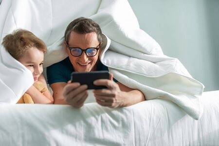 Father and son watching something on smartphone Banco de Imagens