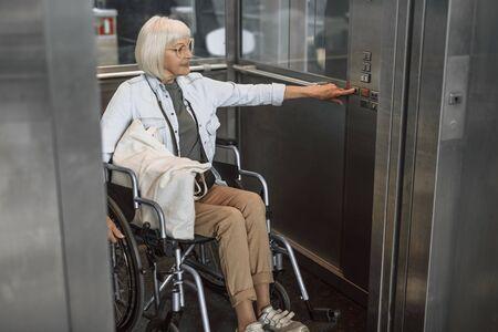 Rijpe vrouw in glazen op gehandicapt vervoer die lift gebruiken Stockfoto