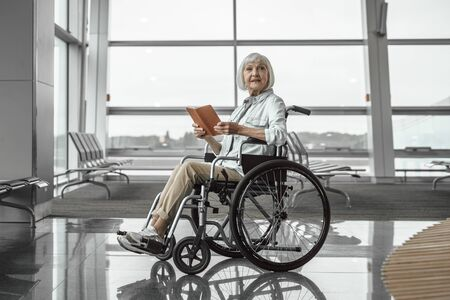 Happy old lady on disabled carriage at waiting room