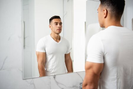 Back side portrait of young man looking at mirror Banco de Imagens