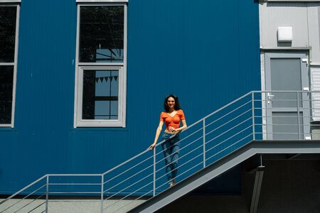 Beautiful young lady with cup of coffee standing on stairs outdoors