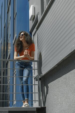 Beautiful young woman with coffee cup leaning on handrail 版權商用圖片