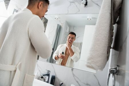 Young happy man with cologne bottle in bathroom
