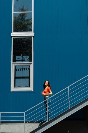 Beautiful young lady standing on stairs against blue wall