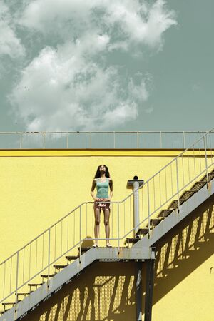 Charming young woman standing on stairs against yellow wall