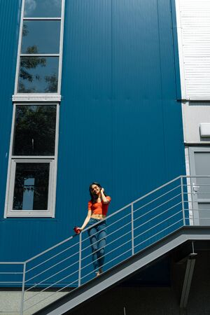 Charming young woman with cup of coffee standing on stairs against blue wall