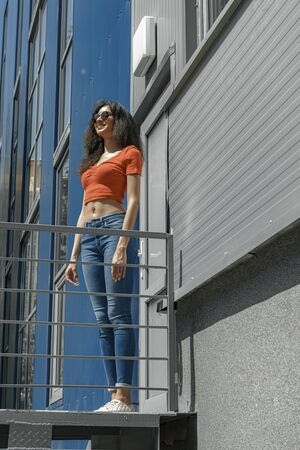 Beautiful young woman standing near modern building on the street