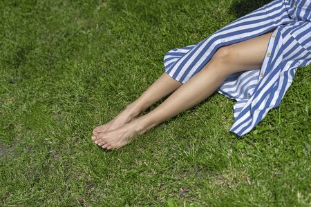 Young woman with bare feet lying on grass