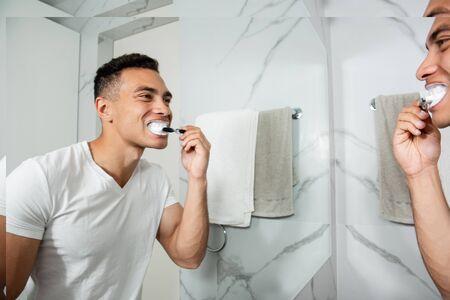 Reflection of smiling handsome man brushing teeth Stock Photo
