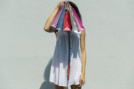Young woman covering face with colorful shopping bags