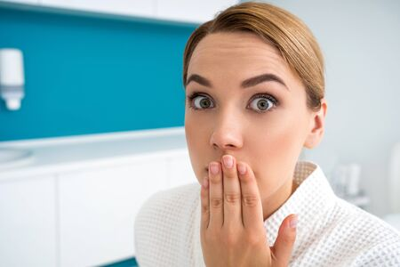 Worried woman closing her mouth in the medical office