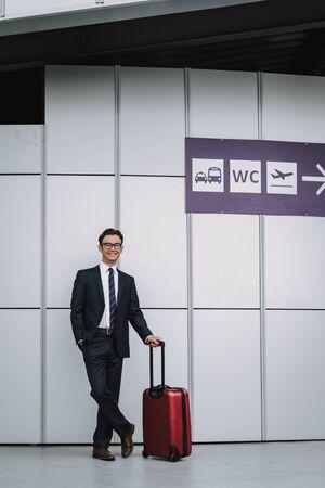 Homme d'affaires souriant en costume sur le parking de l'aéroport