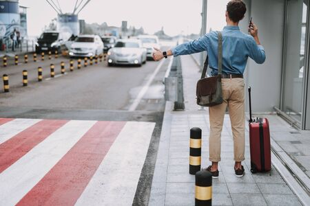 Man in casual wear standing with suitcase near entrance in airport Stock Photo