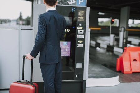 Young guy in suit paying for parking outdoors 写真素材