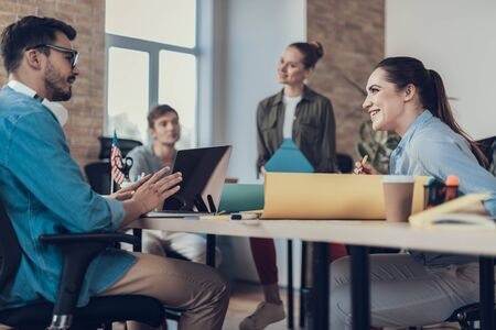 Smiling men and women are working in meeting room Stock Photo