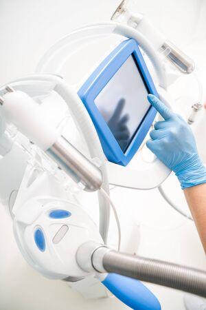 Massagist touching screen of new equipment in massage salon