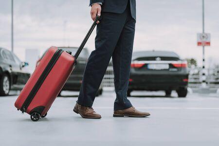 Man in black suit walking on the parking lot