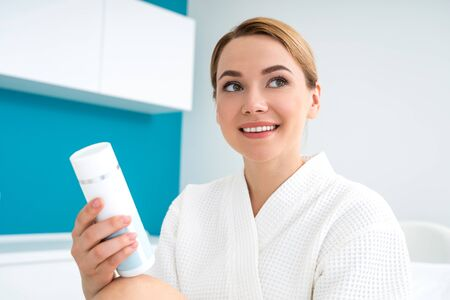 Cheerful lady looking away while holding body lotion 版權商用圖片
