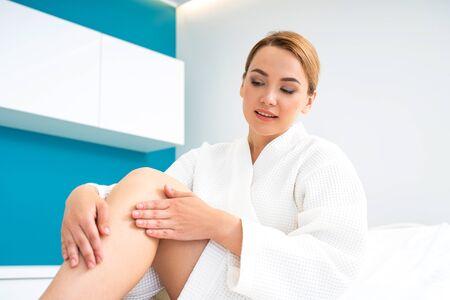 Signora calma che guarda la sua gamba dopo la procedura di depilazione Archivio Fotografico