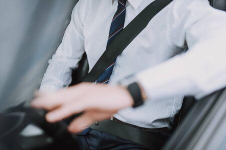 Man in white shirt using seat belt in car Stockfoto