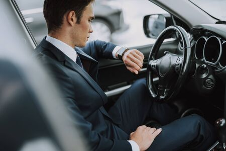 Young man sitting in his car and looking at his watch