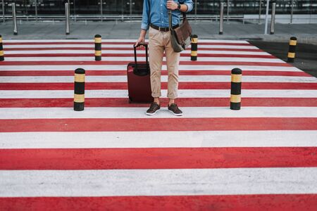 Young man with suitcase standing on crosswalk outdoors Zdjęcie Seryjne