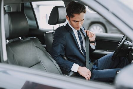 Young man in black suit using seat belt in his auto Фото со стока