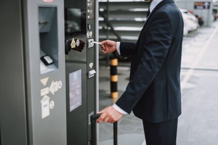 Businessman in suit making payment in the parking meter