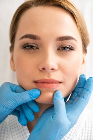 Woman slightly smiling while hands in gloves touching her chin 版權商用圖片
