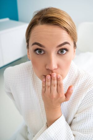 Surprised woman closing her mouth and having eyes wide open Stock Photo - 126060004