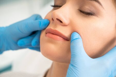 Cosmetologist slightly pulling skin on the face of woman