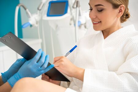 Left handed woman signing agreement in the cosmetologist office Stock Photo