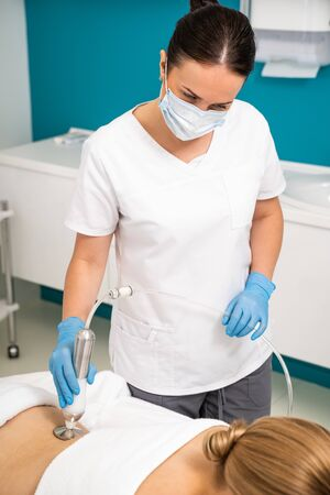 Massaggiatore che fa massaggio con rulli sottovuoto con nuovo apparato per cliente femminile