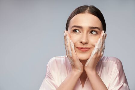 Charming young woman washing face with foaming cleanser