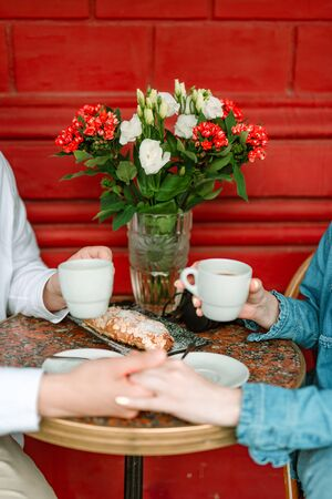 Joyful couple is holding coffee in cafe