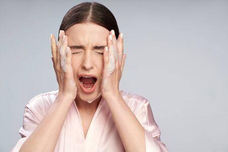 Mujer joven con espuma purificante en la cara cerrando los ojos y gritando Foto de archivo