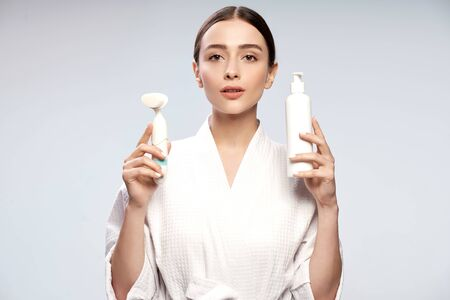 Charming girl holding bottle of cosmetic cream and pore cleansing brush