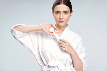 Beautiful young woman in white bathrobe holding pore cleansing brush
