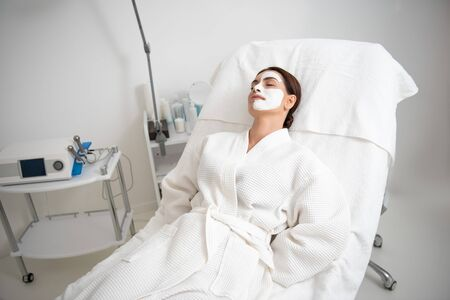 Young female resting on couch with face mask Imagens