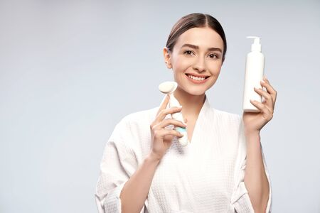 Joyful girl holding bottle of cosmetic cream and pore cleansing brush