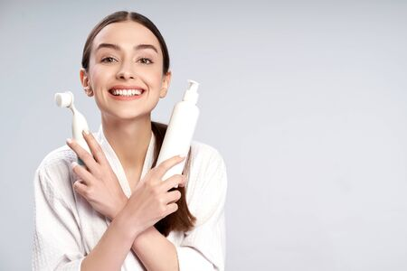 Cheerful girl holding bottle of cosmetic cream and pore cleansing brush 版權商用圖片