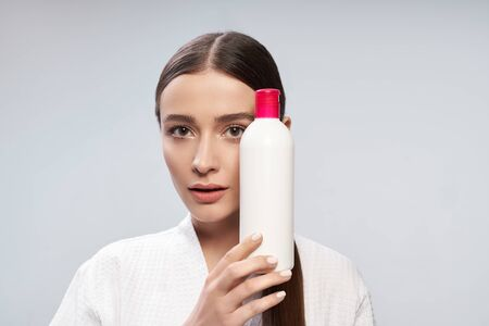 Attractive young woman holding white bottle of cosmetic cream