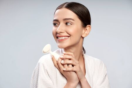 Charming young woman in white bathrobe holding pore cleansing brush